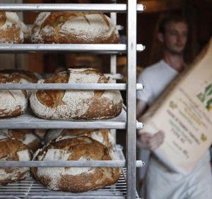 Un Boulanger Francais Transporte Un Sac De Farine Pres De Ses Pains Fraichement Sortis Du Four